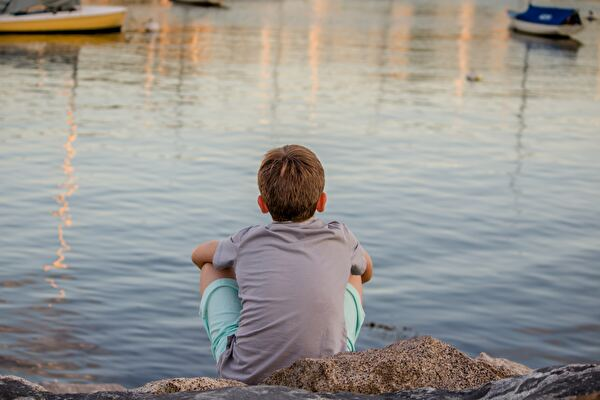 子供が水辺に座っている