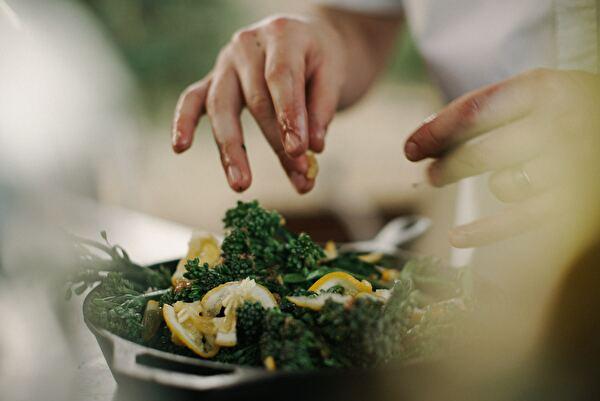 サラダと作っている女性の手