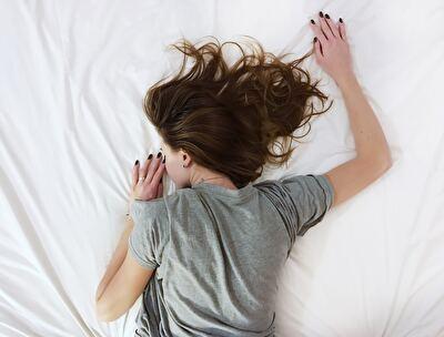 ベッドでうつ伏せになっている女性