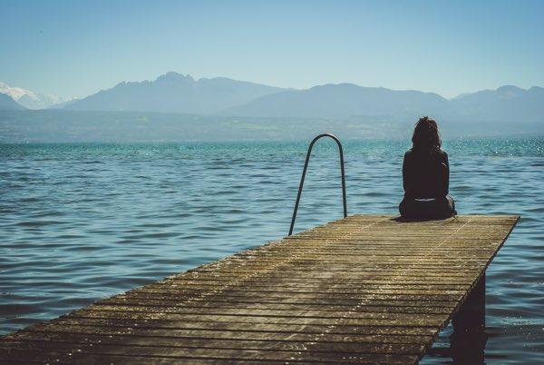 湖の近くに座っている女性