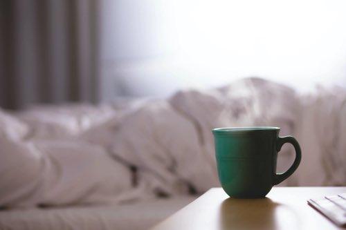 ベッドとコーヒーマグカップ