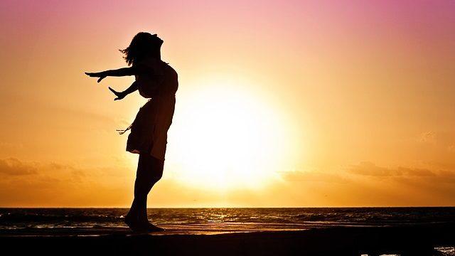 日の光を浴びて気持ちよさそうにたっている女性