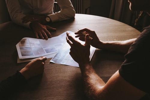 テーブルを囲んで会話をしている3人