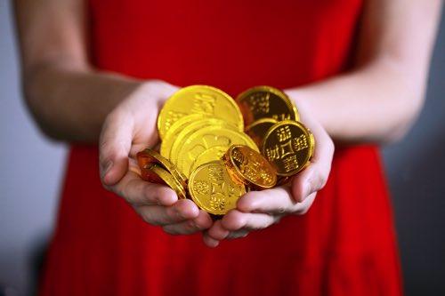 金の硬貨を持つ女性