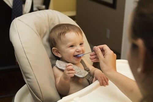 赤ちゃんにスプーンでベビーフードを与えるママ