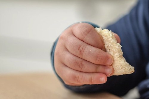 食べ物を掴んでいる赤ちゃんの手
