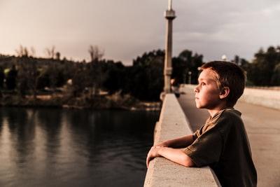 橋の上で考えている男の子
